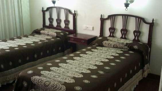 Dormitorio de dos camas color caoba oscuro
